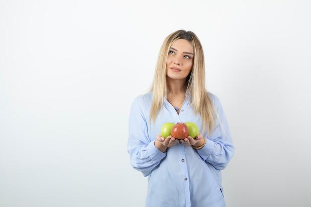 Porträt eines blonden mädchens, das grüne und rote äpfel hält