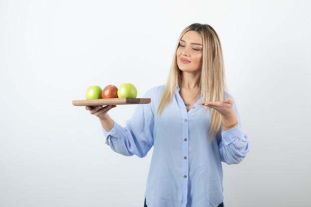 Porträt eines blonden mädchens, das holzbrett mit grünen und roten äpfeln hält