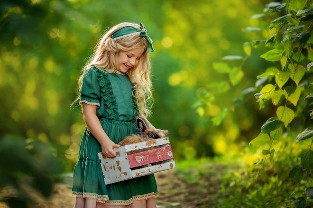 Porträt eines blonden mädchens in einem grünen rustikalen kleid im sommer auf einem spaziergang, der ein kaninchen haustier in einer kleinen holzkiste in händen hält.