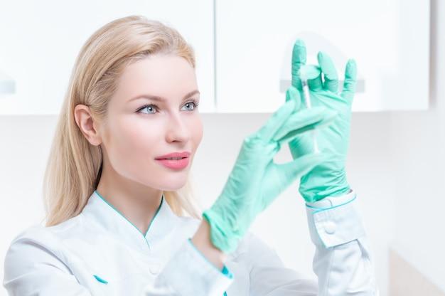 Porträt eines blonden mädchens in einem medizinischen kleid mit einer spritze in ihren händen. werbung für ein medizinisches zentrum. gemischte medien