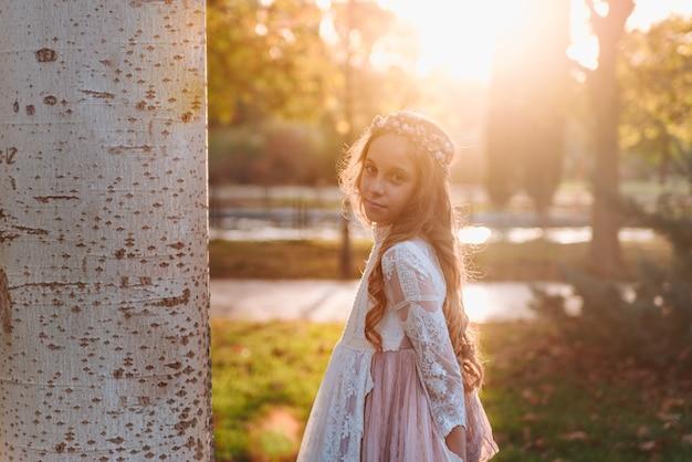 Porträt eines blonden mädchens mit lockigem haar, das bei sonnenuntergang im kommunionkleid gekleidet ist