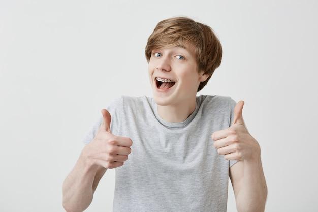 Porträt eines blonden männlichen studenten oder kunden mit einem breiten lächeln, das mit fröhlichem ausdruck in die kamera schaut, mit beiden händen daumen hoch zeigt und die studienziele erreicht. körpersprache