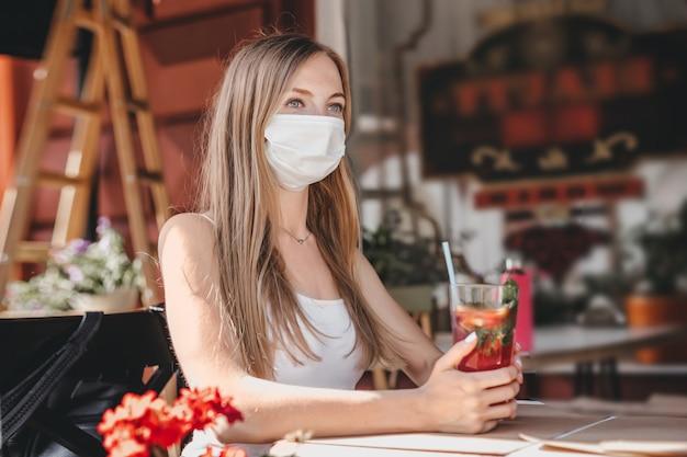 Porträt eines blonden studentenmädchens, das allein in einem café sitzt und eine medizinische maske trägt
