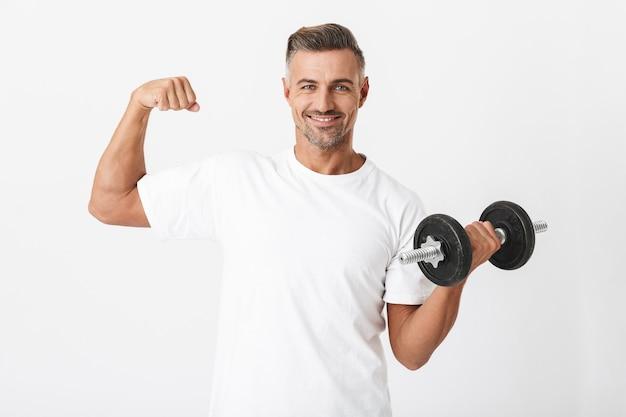 Porträt eines bodybuilder-mannes der 30er jahre mit borsten, der ein lässiges t-shirt trägt, das bizeps pumpt und die hantel einzeln auf weiß hebt
