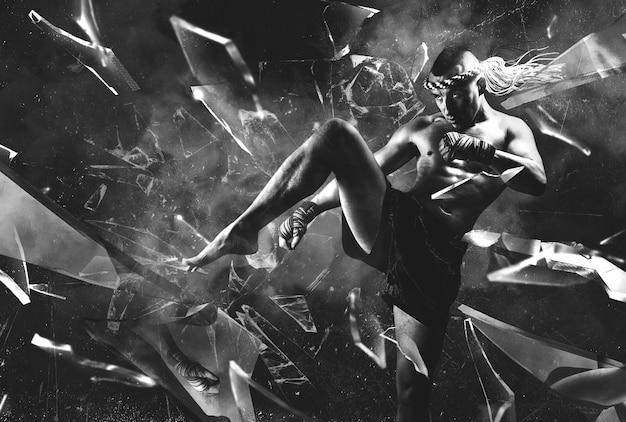Porträt eines boxers der mixed martial arts, der mit seinem knie einen spiegel zertrümmert. das konzept des sports, mma, kickboxen. gemischte medien