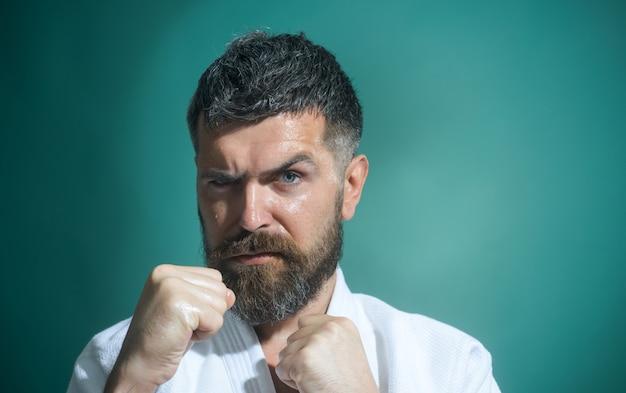 Porträt eines boxers vor dem kampf, nahaufnahme, gutaussehender bärtiger boxer, isoliert auf einem grünen hintergrund brutal