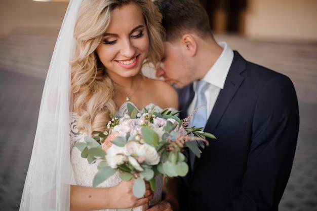 Porträt eines bräutigams, der einen blonden brautschulter küsst