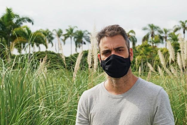Porträt eines brasilianischen mannes, der eine schutzmaske trägt, während er im park steht. porträt eines mittleren erwachsenen mannes im freien, der eine schwarze maske trägt, um sich vor einer coronavirus-pandemie zu schützen. natur im hintergrund.