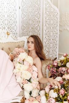 Porträt eines brautmädchens in einem eleganten kleid von rosen, pfingstrosen und blumen
