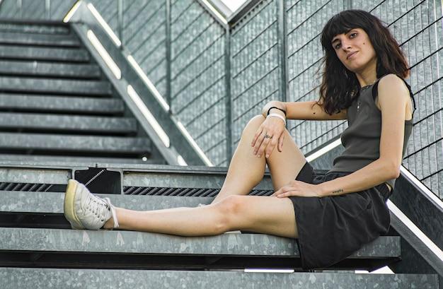 Porträt eines brünetten mädchens, das auf einer städtischen treppe sitzt