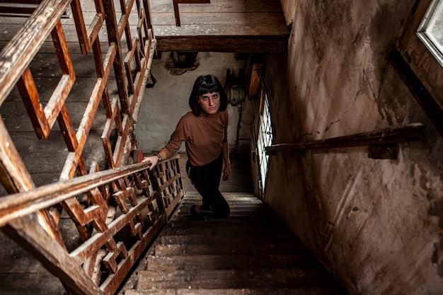 Porträt eines brünetten mädchens in einer treppe eines verlassenen hauses, bild bei schwachem licht Premium Fotos