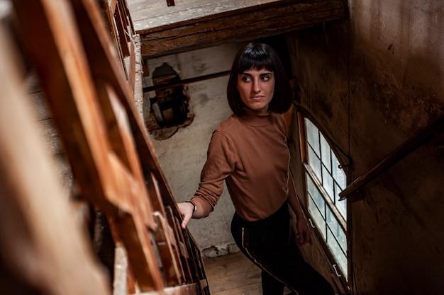 Porträt eines brünetten mädchens in einer treppe eines verlassenen hauses, bild bei schwachem licht