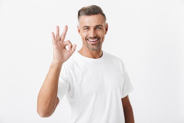 Porträt eines brünetten mannes der 30er jahre mit borsten, der ein lässiges t-shirt trägt, das ein auf weiß isoliertes ok-zeichen zeigt