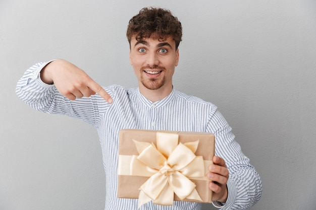 Porträt eines brünetten schönen mannes, der in hemd gekleidet ist und lächelt, während er die geburtstagsgeschenkbox isoliert über grauer wand hält