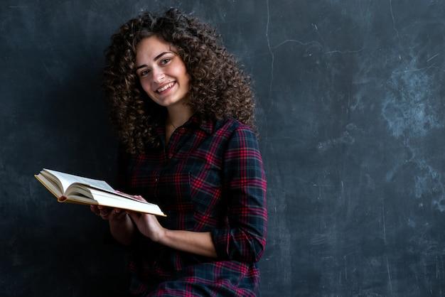 Porträt eines brunettemädchens gegen die graue wand, die ein buch in ihren händen hält, die kamera lächelt und betrachtet