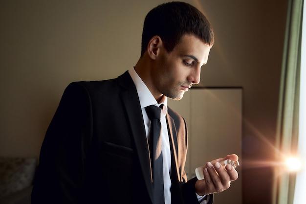 Porträt eines brutalen mannes mit köln in den händen, parfümduft für echte männer, parfümkosmetik. parfüm köln flasche. fashion cologne flasche reicher mann
