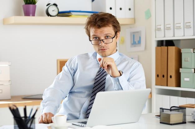 Porträt eines buchhalters oder wirtschaftsprüfers, der an seinem arbeitsplatz sitzt. geschäftsmann in seinem büro.
