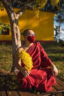Porträt eines buddhistischen mönchs, der blumen hält
