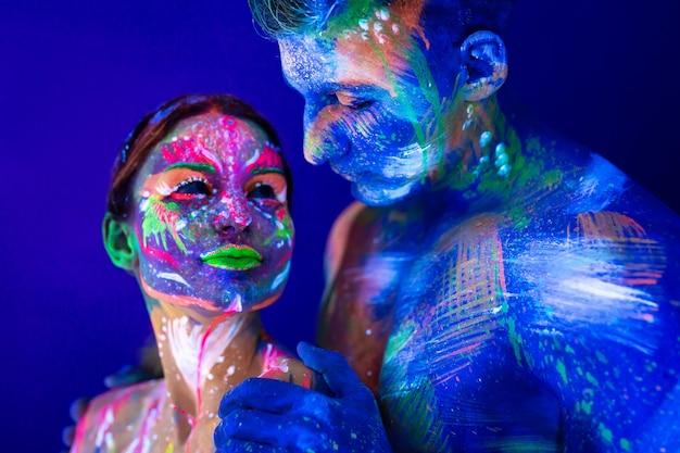 Porträt eines bulligen mannes und einer frau, die in ultraviolettem pulver gemalt werden. körperkunst, die im ultravioletten licht leuchtet