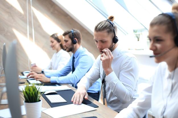 Porträt eines call-center-mitarbeiters in begleitung seines teams. lächelnder kundendienstmitarbeiter bei der arbeit.