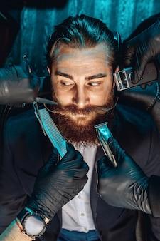 Porträt eines charismatisch attraktiven mannes mit schnurrbart und bart, der auf einem sessel in einem friseursalon sitzt. um sein gesicht, schere, rasierer. männliches schönheitskonzept