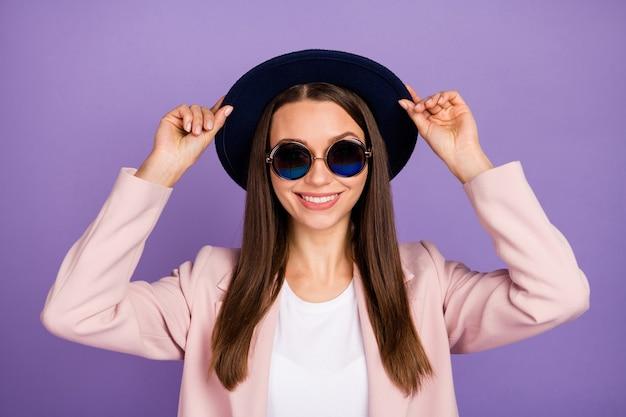 Porträt eines charmanten, attraktiven mädchens, das ihren retro-hut berührt, genießen sie die freizeit am herbstwochenende und tragen sie pastellkleidung einzeln auf violettem farbhintergrund
