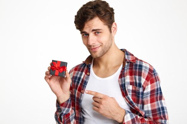 Porträt eines charmanten brünetten mannes, der finger zeigt