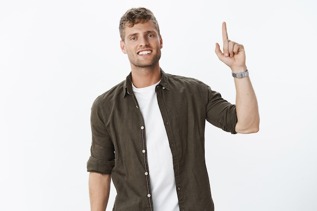 Porträt eines charmanten, freundlich aussehenden männlichen mannes mit borsten und weißem lächeln, der nach oben zeigt, mit erhobenem zeigefinger, der die aufmerksamkeit auf die förderung über grauer wand bittet