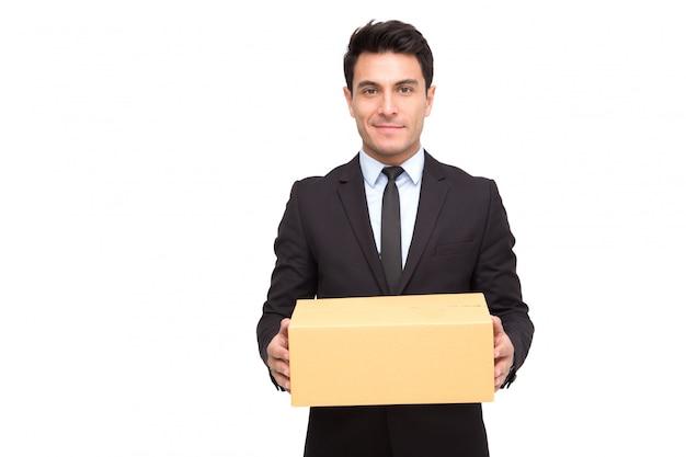 Porträt eines charmanten geschäftsmannes gekleidet im anzug, der paket hält, während er steht und kamera lokalisiert über weißem hintergrund betrachtet.