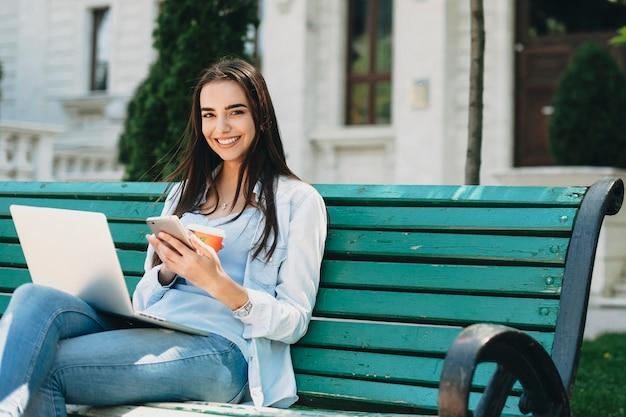 Porträt eines charmanten langhaarigen mädchens, das an einem strand sitzt und mit einem smartphone die kamera betrachtet, die gegen ein gebäude mit einem laptop auf ihren beinen lacht.