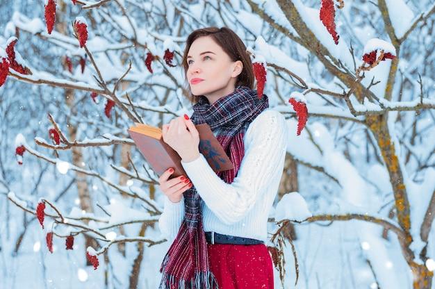 Porträt eines charmanten mädchens, das im winterwald ein buch liest.