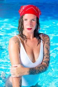 Porträt eines charmanten mädchens im zigeunerstil, das im pool schwimmt