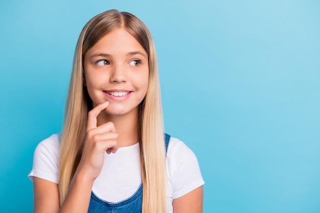 Porträt eines charmanten, positiven teenie-mädchens, das einen leeren raum sieht, trägt ein lässiges outfit, das auf pastellblauem hintergrund isoliert ist