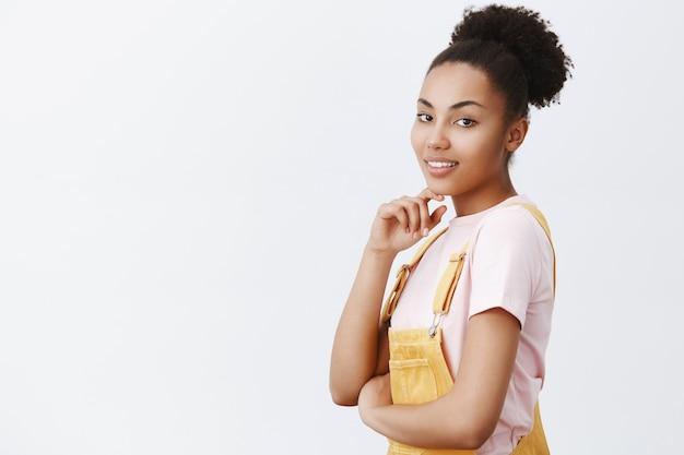 Porträt eines charmanten sinnlichen weiblichen mädchens in gelben overalls, das halb gedreht steht und sanft blickt und das kinn berührt