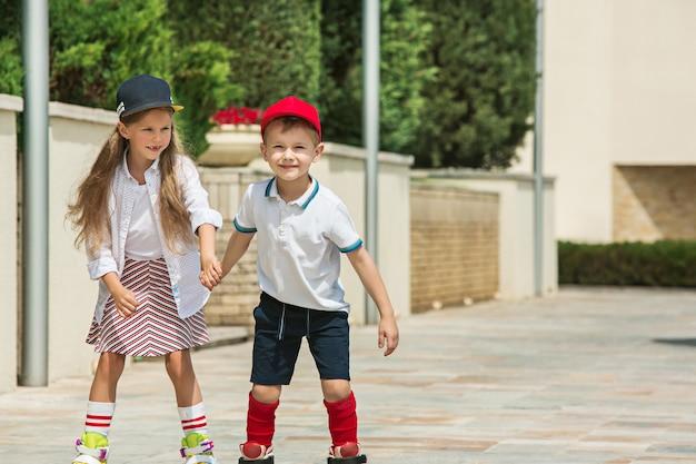 Porträt eines charmanten teenagerpaares, das zusammen auf rollschuhen am park skatet. teen kaukasischen jungen und mädchen. kinder bunte kleidung, lebensstil, trendige farbkonzepte.