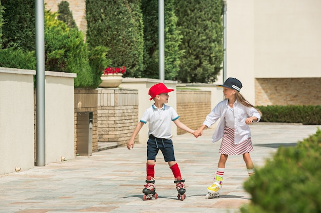 Porträt eines charmanten teenagerpaares, das zusammen auf rollschuhen im park skatet. teen kaukasischen jungen und mädchen