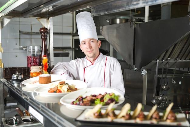 Porträt eines chefs mit gekochtem essen in der küche im restaurant.