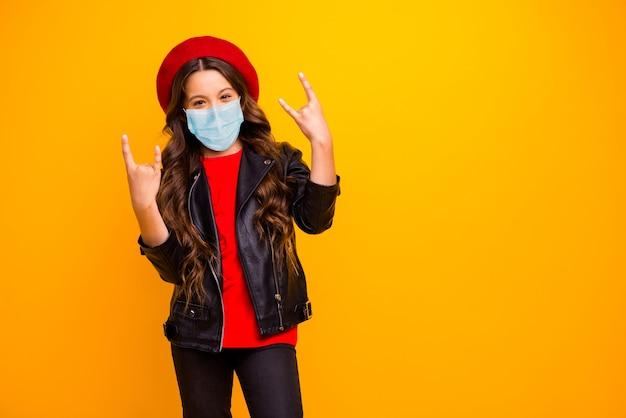 Porträt eines coolen langhaarigen mädchens, das eine sicherheitsmaske trägt, um die grippe zu stoppen, zeigt ein hornzeichen