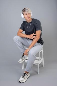 Porträt eines coolen teenagers mit kopfhörern, die auf einem stuhl posieren