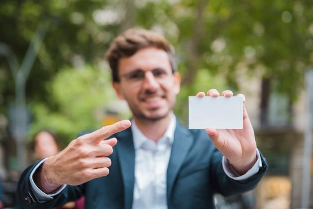 Porträt eines defokussierten jungen geschäftsmannes, der seinen finger in richtung zur weißen visitenkarte zeigt