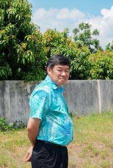 Porträt eines dicklichen älteren asiatischen mannes, der im greenfield-grasgarten steht und lächelt