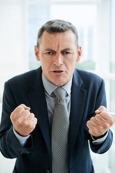 Porträt eines die stirn runzelnden reifen chefs in formellem anzug, der die hände zu fäusten ballt, während er ihnen eine inspirierende rede sagt