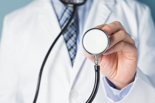 Porträt eines doktors, der stethoskop für körperliche untersuchung hält