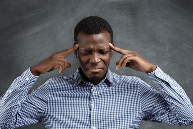 Porträt eines dunkelhäutigen unternehmers, der starke kopfschmerzen hat, die finger gegen seine schläfen drückt, die augen schließt und sich mit schmerzhaftem ausdruck verzieht.