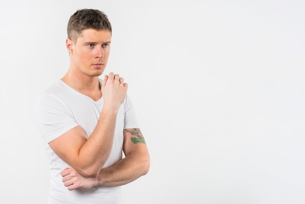 Porträt eines durchdachten jungen mannes, der gegen weißen hintergrund steht