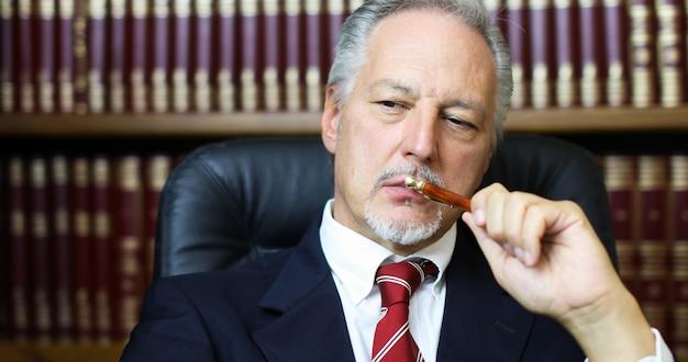 Porträt eines durchdachten managers in seinem büro, das einen stift hält