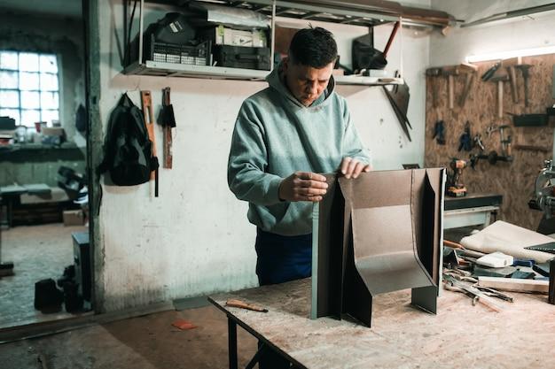 Porträt eines echten blechschmieds eines mannes, der in seiner werkstatt mit metall arbeitet,