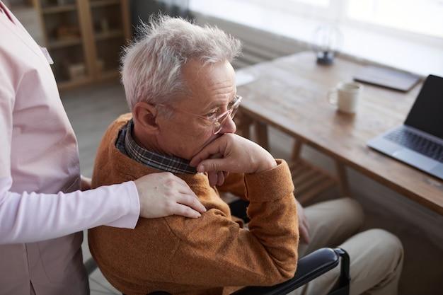 Porträt eines einsamen älteren mannes im rollstuhl im altersheim mit einer krankenschwester, die ihn tröstet, kopienraum