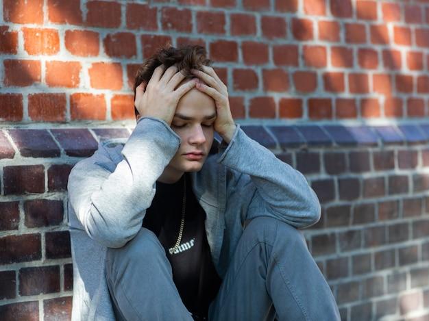 Porträt eines einsamen traurigen teenagers in einem hoodie mit einer kapuze auf der straße, probleme und psychologie von jugendlichen, konzept. junger mann hält seinen kopf