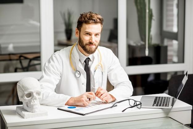 Porträt eines eleganten leitenden arztes im medizinischen kittel, der im büro mit dokumenten und laptop arbeitet